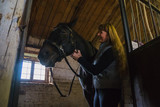 The horse and groom in the stable in the weak light - 182985867