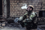 Special forces soldier after the fight sitting in ruined building smoking cigarette staring at the camera - 182987837