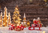 Holidays background with illuminated Christmas tree, sledge with gifts and wooden village. - 182989222