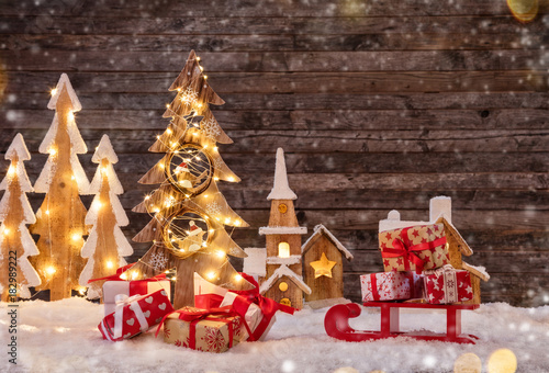 Holidays background with illuminated Christmas tree, sledge with gifts and wooden village.