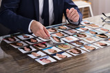 Businessperson Choosing Photograph Of Candidate