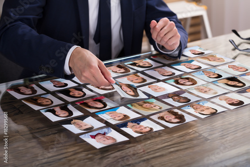 Businessperson Choosing Photograph Of Candidate - 182995681
