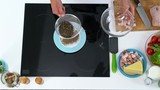 Top view of hands of unrecognizable male cook sieving peppercorn into plate standing on induction cooker; cheese, chopped meat and fresh vegetables lying on kitchen table - 182997431
