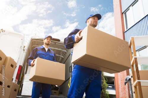 Fototapeta Close-up Of Two Delivery Men Carrying Cardboard Box