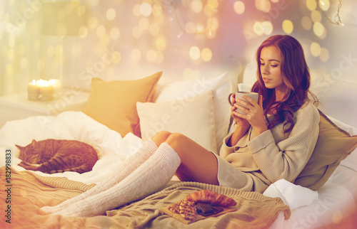 happy woman with cup of coffee in bed at home - 182998833
