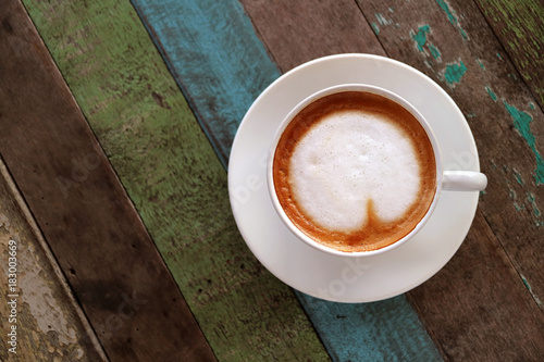 Papiers peints Cafe Top view of hot coffee with heart shaped latte art in white cup served on colored rustic style wooden table