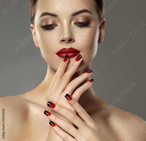 Foto op Plexiglas Manicure Beautiful model girl with red and black french manicure on nails . Fashion luxury makeup . Beauty and cosmetics .