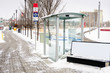 Deserted Bus Stop with a Glass Shelter in Calgary, Canada, on a Snowy Winter Day