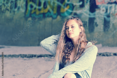 Girl teenager with flowing brown hair sitting against concrete wall