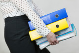 Woman holding heavy colorful binders with documents - 183029099