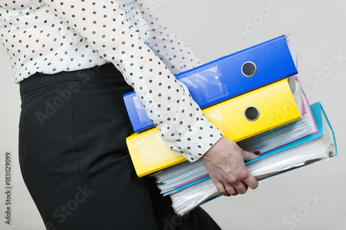 Fototapeta Woman holding heavy colorful binders with documents