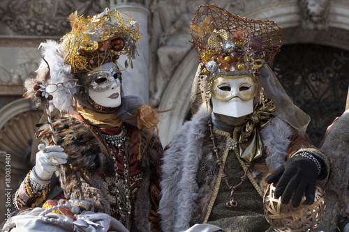 Venice Carnival characters in a colorful brown and gold Carnival costumes and masks Venice Italy - 183033480