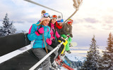 cheerful friends are lifting on ski-lift for skiing in the mountains - 183033827