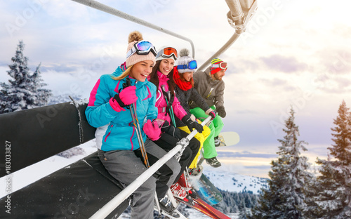 cheerful friends are lifting on ski-lift for skiing in the mountains