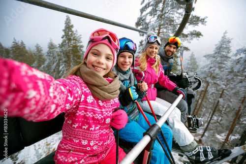 Skiing, ski lift, ski resort - happy family skiers on ski lift making selfie