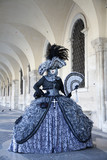 Venice Carnival figure in colorful costume and mask, under the Arcade of the Doge's Palace Venice Italy