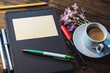 album, pens and pencils on a wooden table. a cup of coffee with milk.