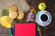 a notebook, a cup of coffee and oatmeal cookies on a wooden table. place for text.