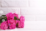 Bunch of pink  roses  flowers on white wooden background against white wall.
