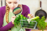 Woman looking through magnifier at vegetables basket - 183049048