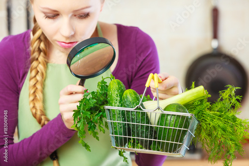 Woman looking through magnifier at vegetables basket
