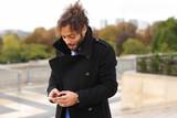 Mulatto laughing guy around Eiffel Tower with smartphone