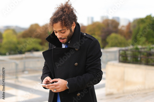 Mulatto laughing guy around Eiffel Tower with smartphone