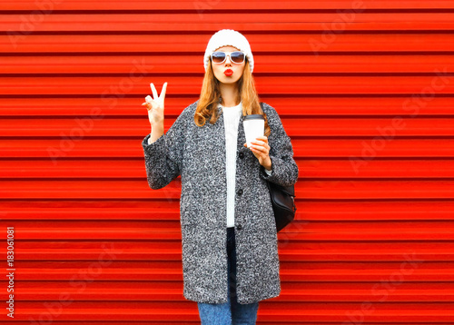 Fashion pretty woman with coffee cup in coat posing on red background - 183061081