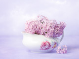 Still life  with small  branch of lilac  in  old porcelain gravy boat on light violet background. - 183061241