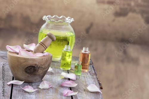 In de dag Spa Spa and wellness concept: preparation of essential oil with pink roses, bottle of tincture and mortar on a wooden board with all vintage wall