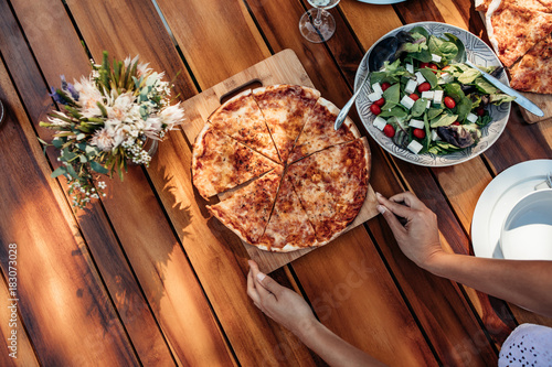 Woman setting the pizza on table for dinner Poster