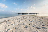 Maldives water bungalow on ocean water landscape. Crabs holes on beach sand in the foreground. - 183074048