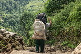 Man with sack on Annapurna trekking route. - 183078064