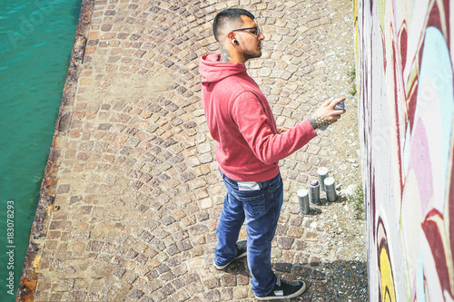 Street graffiti artist painting with a color spray can a graffiti mural on the wall - Urban, lifestyle, street art concept - 183078293