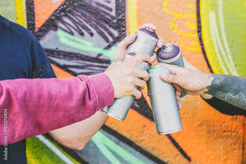 Close up hands of people holding color spray cans against the graffiti wall - Graffiti artists at work - Rebels, lifestyle, street art concept - Focus on can spray on the right - 183078404
