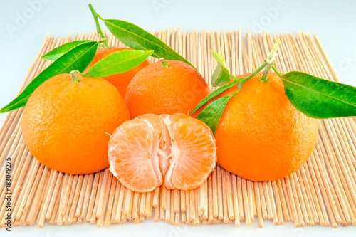 Tangerines with leaves and slices on wooden sticks - 183079275