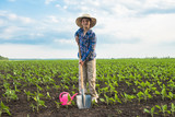 Happy small farmer with spade in spring field - 183084888