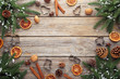 Fir-tree branches with dried orange, walnut and cinnamon on wooden table