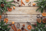 Fir-tree branches with dried orange, walnut and cinnamon on wooden table - 183088657