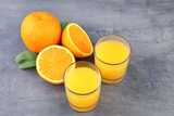 Glass of orange juice on grey wooden table - 183088863