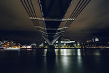 Long exposure shot taken underneath the Millennium Bridge on River Thames in London at night