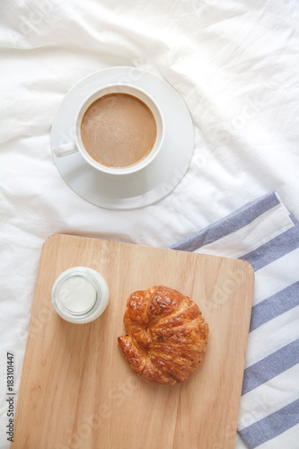 Fototapeta Bed breakfast with coffee cup, croissants and milk in bed, cozy relaxing morning coffee, holidays and winter concept