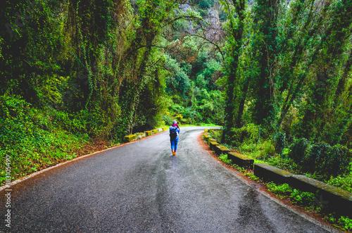 In de dag Weg in bos Mujer camina por una carretera de montaña