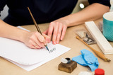 arts and crafts, hobby, talent concept. caucasian woman calligrapher is writing with old style quill and beautiful blue inks on the table with all equipment for art - 183106664