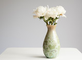 Closeup of white peonies in green vase on table against grey background with copy space - 183108819