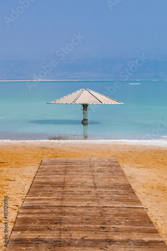 Wood planks track through the beach to umbrella into Dead sea to safe people agains the hot sun