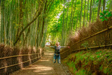 Happy tourist woman jumping in bamboo forest at Sagano in Arashiyama, kyoto, japan. Travel asia concept. Freedom and enjoying concept. Kyoto's popular landmark and touristic destination.