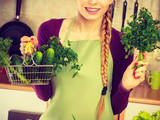 Woman in kitchen having vegetables holding shopping basket - 183122471