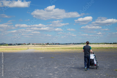 Fotobehang Berlijn Young male tourist visiting Tempelhofer Feld in Berlin with a stroller and his child