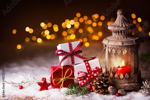 Christmas gifts and lantern in snow landscape with bokeh background